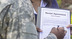 Soldier in uniform signing a lease or rental agreement held by a realtor or landlord