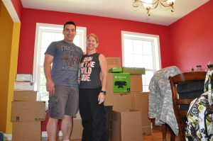 New York Army National Guard Majs. Brian Bonanno (left) and Amy Bonanno (right) are among boxes of their household goods at their home in Clifton Park, N.Y., July 20, 2015, as they pack for a move to South Africa. The two veterans, both staff officers in the New York Army National Guard's 42nd Infantry Division, are heading with their two children to Pretoria, South Africa, where Brian will be the liaison officer for the New York Army National Guard and South Africa State Partnership Program. (U.S. Army National Guard photo)