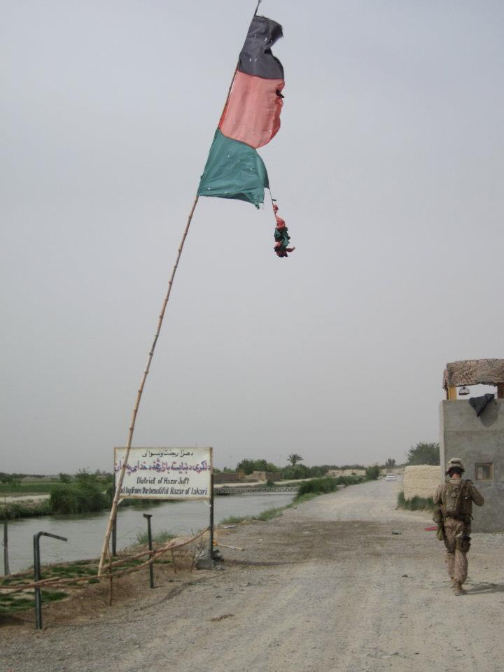 Lone Marine walking along a canal in Afghanistan under a tattered flag