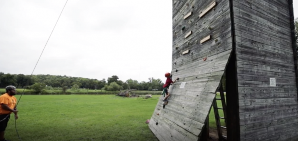 Military kid climbing wall at YMCA summer camp