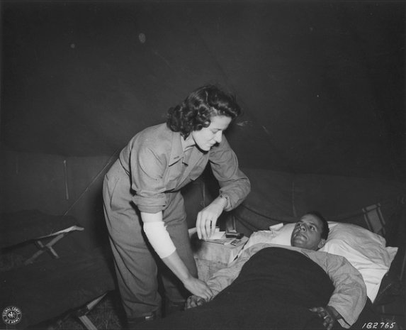 First Lieutenant Cordelia E. Cook (first woman awarded Purple Heart and Bronze Star, her right arm injured by German shrapnel, tends one of her fellow wounded.
