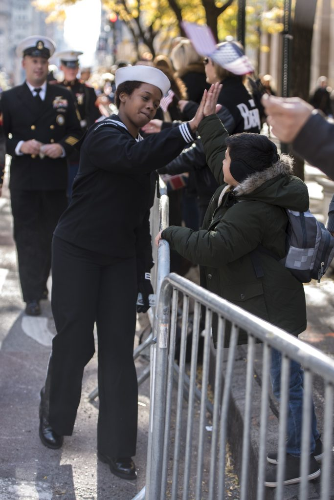 U.S. Navy Boatswain's Mate 3rd Class Zatyra Rousseau of Patterson, N.J. high fives a parade guest during the 2018 Veterans Day Parade. Rousseau serves aboard USS Dwight D. Eisenhower (CVN-69). Veterans Week New York City 2018 honors the service of all our nation's veterans. Veterans Week events include a port visit from USS Oak Hill (LSD 51), a ceremony and parade on Veterans Day and numerous opportunities for Sailors to enjoy liberty around the city of New York.  (U.S. Navy photo by Chief Mass Communication Specialist Roger S. Duncan)