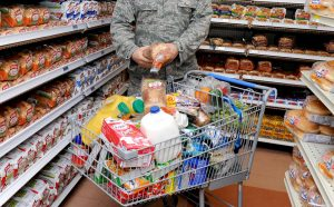 Second Lt. Ben Garland, 375th Air Mobility Wing public affairs chief of media operations, tops off his shopping cart stuffed with groceries with two loaves of bread at the Commissary, March 9, 2012, at Scott Air Force Base, Ill. Garland shops each week to fuel his 6,000 to 8,000 calorie daily intake. On average his spends $200 each week.